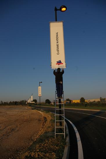 Fase di applicazione di polionda nei banner montati sui pali della luce.